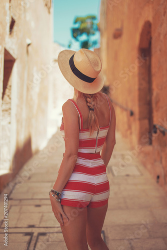 Blonde woman in hat on old mediterranean street © sakkmesterke