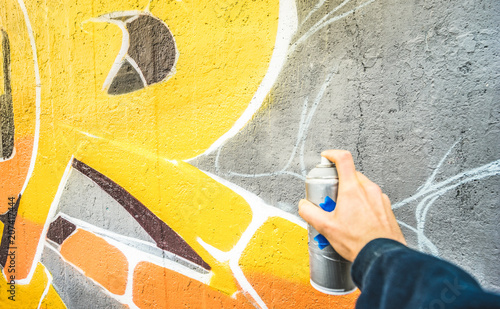 Fotobehang Graffiti Detail of street artist painting colorful graffiti on public wall - Modern art concept with urban guy drawing live murales with multi color aerosol spray - Vintage filter with focus on yellow paint