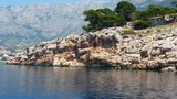 View from a boat in the sea coming around a rocky coast revealing the city of Makarska Croatia - 207420807