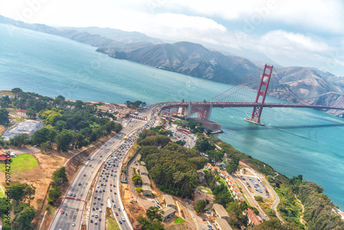 Aerial overhead view of San Francisco Golden Gate Bridge and city traffic from helicopter