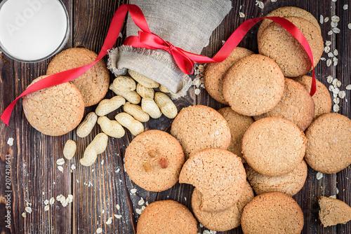 Sticker Homemade oatmeal cookies with raisins, cinnamon with milk on dark wooden background.