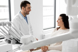 medicine, dentistry and healthcare concept - male dentist talking to female patient and discussing teeth treatment at dental clinic office - 207429879
