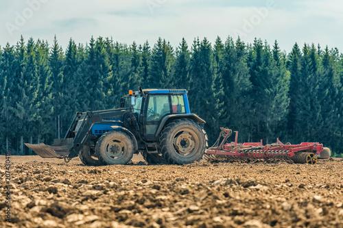 Fotobehang Trekker Picture of farmer plowing stubble field