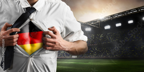 Leinwanddruck Bild Germany soccer or football supporter showing flag under his business shirt on stadium.