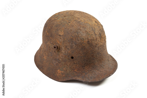 Vintage M1916 German Imperial Army steel helmet, or stahlhelm, used in World War I in rusty condition, isolated on white