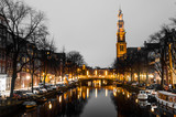 Sunrise on a canal with old historical church on the horizon in Amsterdam water Holland bridge