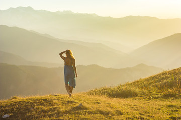 girl in dress standing on grass in sunset mountains