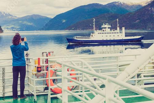Fototapeta Tourist woman on liner taking photo, Norway