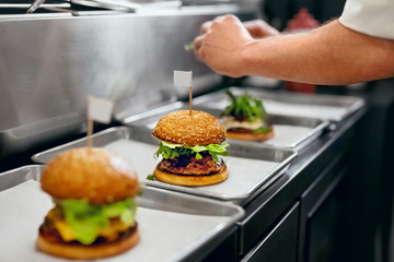 Burger Restaurant. Closeup Chef Cooking Burgers In Kitchen.