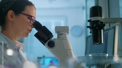 Young life scientist looking through a microscope in a laboratory.