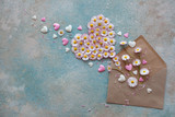 Background with flowers daisies in the shape of heart and envelope