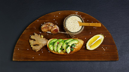 bruschetta, sandwiches with avocado, garlic, lemon and ginger on wooden board, on a shale, the concept of healthy eating, copy space, top view, set
