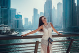 Happy beautiful unrecognizable tourist woman in fashionable summer white dress