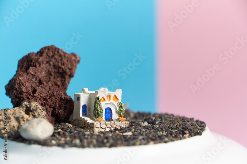 Fotobehang Lichtroze Animated model of a Greek house on a rock on a neon and pink background.