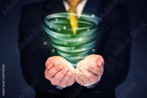 Foto Murales Bright green tornado in the hands of a businessman