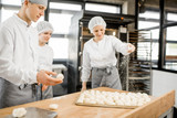 Bakers sprinkling flour on the dough balls preparing for baking buns at the manufacturing - 207550651