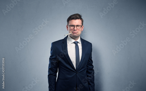 Leinwanddruck Bild Young tired businessman with thermometer and copy space
