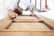 Leinwanddruck Bild - carpenter work the wood with the sandpaper