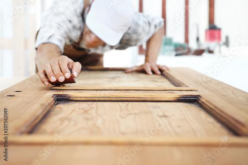 Leinwanddruck Bild carpenter work the wood with the sandpaper