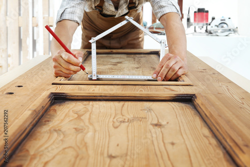 Leinwanddruck Bild woodwork concept, carpenter with the meter makes the shape of a house