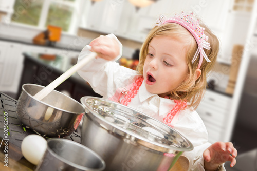 Foto Murales Cute Baby Girl Playing Cook With Pots and Pans In Kitchen