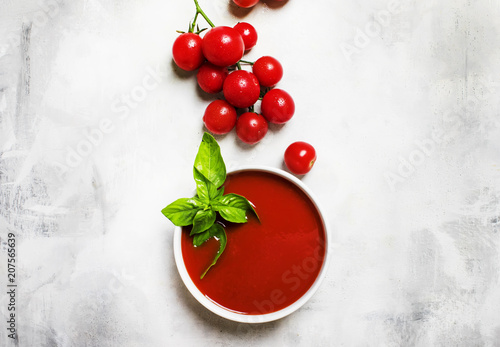 Homemade tomato soup with green basil, top view