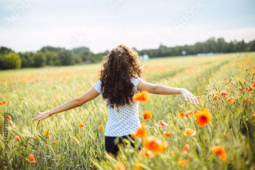 Schöne junge Frau läuft mit offenen Armen voller Freude durch ein Mohnblumenfeld