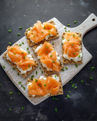 Homemade Crispbread toast with Smoked Salmon and soft chees, chives on white board