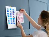 inspiration art painting. painter workspace decor. woman sticking drawing and color swatch palette to the blue wall