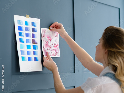 Fototapeta inspiration art painting. painter workspace decor. woman sticking drawing and color swatch palette to the blue wall
