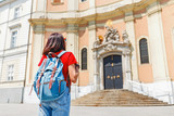 rear view of a tourist woman with backpack looking at historical architecture of a catholic church, sightseeing tour concept