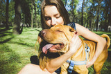 A beautiful girl hugs her dog sharpei breed. the dog is a devoted friend of the girl. portrait with pet - 207603230