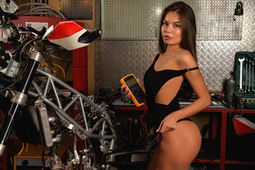 Girl with tester repairing motorcycle