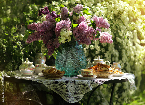 A bouquet of lilac in a glass vase. Tea in the garden.