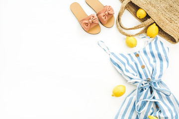 Summer female fashion stylish composition. Dress, slippers, straw, lemons, tulip flower and accessories on white background. Flat lay, top view.