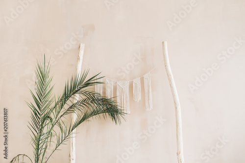 Minimal home interior design. Tropical palm branches and boho decoration at pastel beige wall. Modern studio concept.