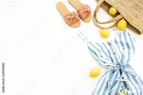 Leinwanddruck Bild Summer female fashion stylish composition. Dress, slippers, straw, lemons, tulip flower and accessories on white background. Flat lay, top view.