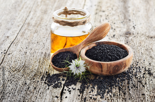 Black cumin oil with flower on wooden background © Dionisvera