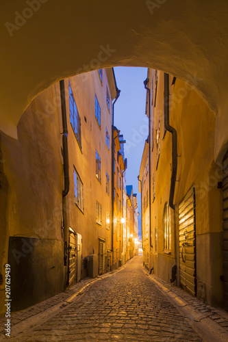 Fotobehang Stockholm Night view of narrow alley connecting with archway passage street with historic town houses of colored facade illuminated by lights in the Old city (Gamla Stan) of Stockholm, Sweden.