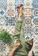 Leinwanddruck Bild - Lazy morning on terrace. Flat-lay of womans legs in cosy linen pants, plant, cat and cup of coffee in hand over colorful moroccan tile floor, top view