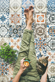 Lazy morning on terrace. Flat-lay of womans legs in cosy linen pants, plant, cat and cup of coffee in hand over colorful moroccan tile floor, top view - 207640695