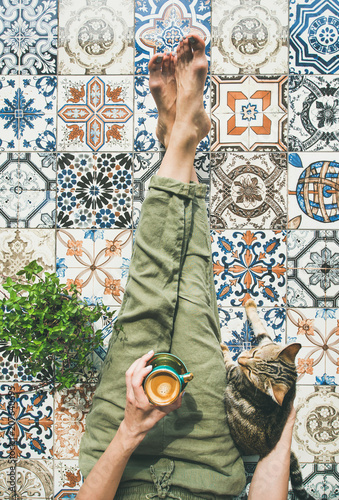 Leinwanddruck Bild Lazy morning on terrace. Flat-lay of womans legs in cosy linen pants, plant, cat and cup of coffee in hand over colorful moroccan tile floor, top view