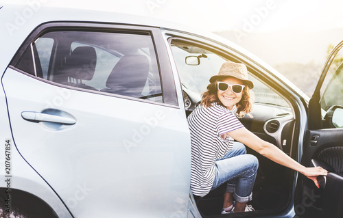 Young beautiful female travel girl in hat and sunglasses speaks by mobile phone on the background of her car while traveling in the mountains, renting and car service