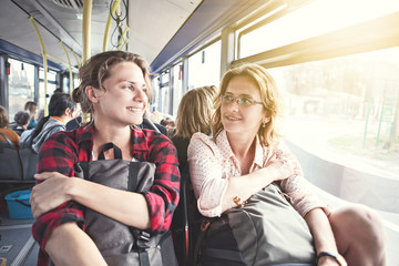 Two girls travel with backpacks by bus, public transport, travel and vacation, friendship