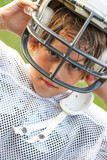 Young boy in a football uniform taking off his helmet after a game - 207649466