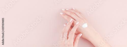 Leinwanddruck Bild Woman moisturizing her hand with cosmetic cream