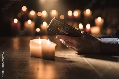 Leinwanddruck Bild Man reading the Holy Bible and praying in the Church