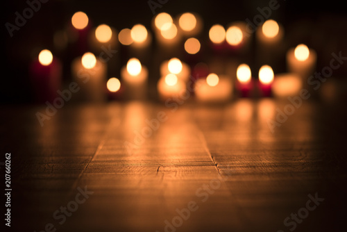 Leinwanddruck Bild Lit candles burning in the Church