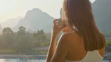 Young woman drinking hot coffee on the balcony with beautiful mountain landscape - 207673297