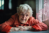 Old woman sitting near window, close-up portrait. - 207674081